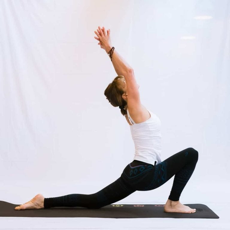 A yoga teacher doing a Hatha yoga sequence in a crescent lunge showing the physical aspect of Hatha Yoga vs Kundalini Yoga
