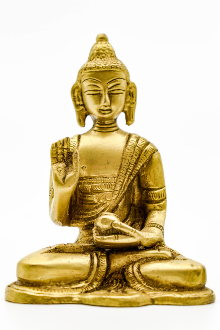 A bronze buddha statue holding his hand up in a blessing. The other hand holds medicine. He is seated.
