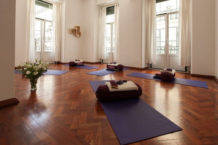 Amazing yoga studios in lisbon a yoga studio with a dark wood floor and high ceilings with mats arranged with bolster cushions