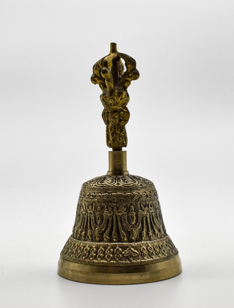 A carved meditation bell in matte gold with a handle shaped as a varja